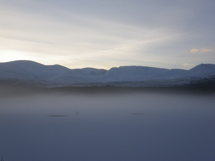 Early morning light on the Cairngorms from a mist covered Loch Morlich