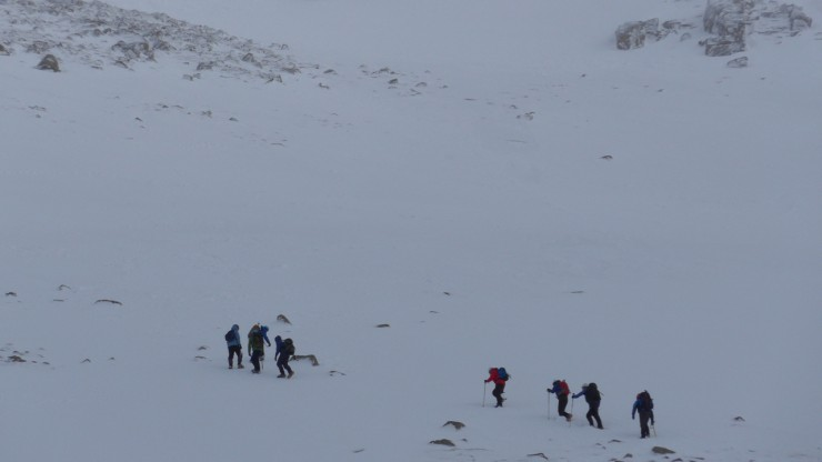 Party heading up to windy Col on firm snow - Sneachda